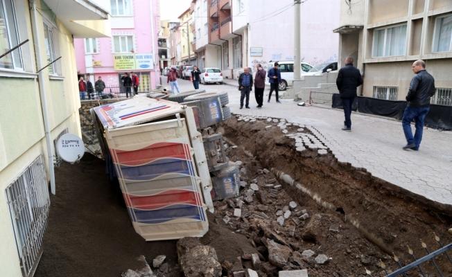 Kum yüklü kamyon, apartmanın bahçesine devrildi